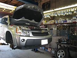 A car on a lift getting expert care at Dick's Auto Service of Clinton